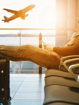 Man sitting at the airport watching an airplane